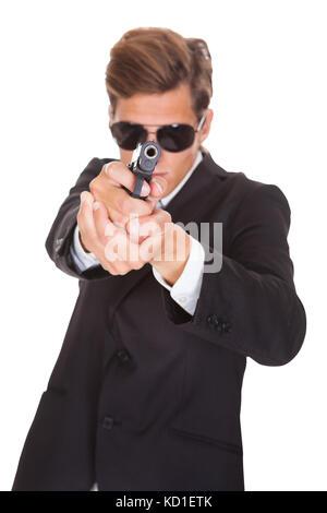 Agente segreto indossando occhiali da sole mirando con la pistola verso la telecamera Foto Stock