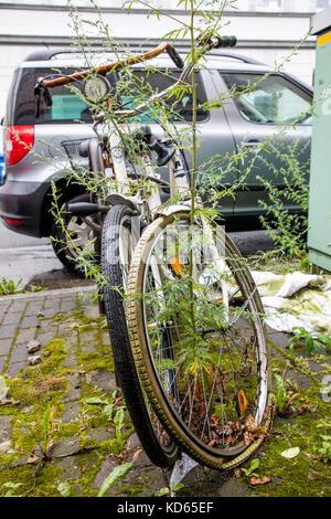 Il parcheggio per le bici sorge in una città, biciclette sono ricoperta da piante, biciclette parcheggio qui per Foto Stock