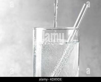 Dettaglio di acqua frizzante è versata in un vetro trasparente con una cannuccia trasparente su un metallo grigio Foto Stock