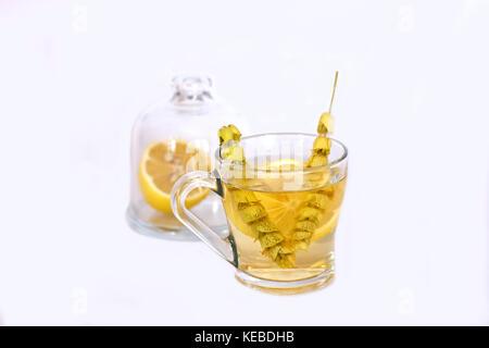 Il tè caldo con la salvia e limone nella tazza di vetro. Foto Stock