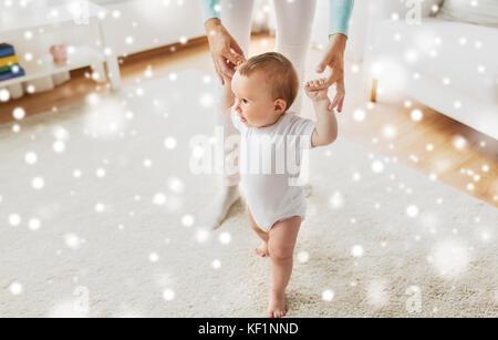 Happy baby ad imparare a camminare con la madre aiutare Foto Stock