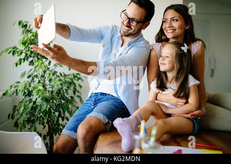La famiglia felice tenendo selfie nella loro casa Foto Stock
