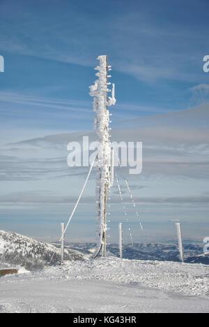 Antenna di telecomunicazione sulla cima della montagna, congelati e completamente coperto di neve e ghiaccioli contro Foto Stock