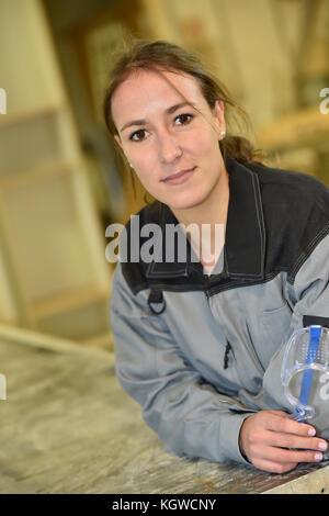 Giovane donna in officina appoggiata sul banco di lavoro Foto Stock