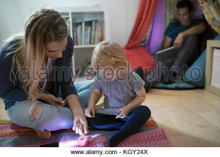 La bionda madre e figlia toddler giocando con il giocattolo sul pavimento della camera Foto Stock