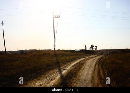 Silhouette di quattro ciclista in piedi su un open strada di ghiaia Foto Stock