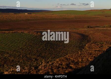Vista dal vallo di Adriano guardando a nord su campagna con un fienile solitario in golden luce della sera con acciaio Foto Stock