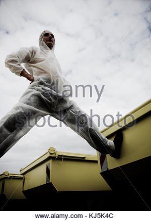Uomo in tuta protettiva in piedi a cavallo di contenitori Foto Stock