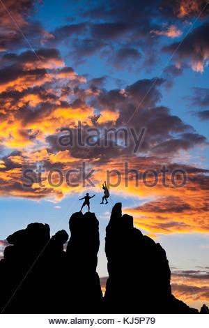 Scalatore salta da una roccia per un altro Foto Stock