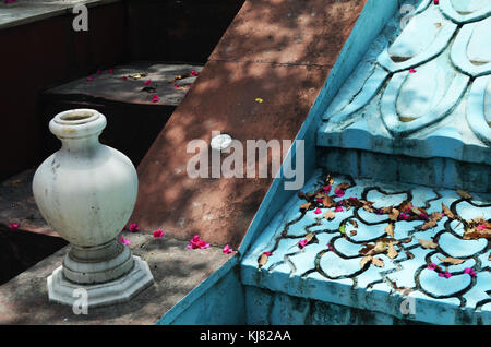 Fontana inutilizzati coperti con petali in un tempio indù in India. Foto Stock