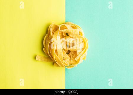 Lay piatto di tagliatelle sul doppio sfondo colorato. Foto Stock