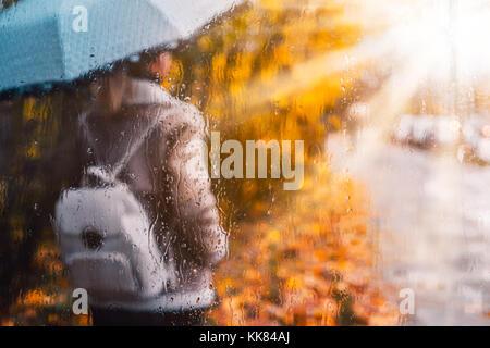 Golden stagione autunnale. Acquerello come sfocata ragazza bionda con zaino e ombrello luminoso sorge sotto le gocce Foto Stock