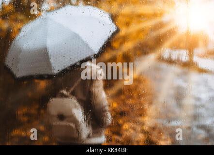 Beautiful golden stagione autunnale. Acquerello come sfocata ragazza bionda con zaino e ombrello luminoso sorge Foto Stock