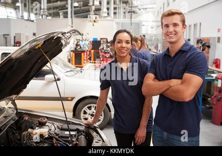 Due Apprendisti meccanici cercando di fotocamera accanto a un auto Foto Stock