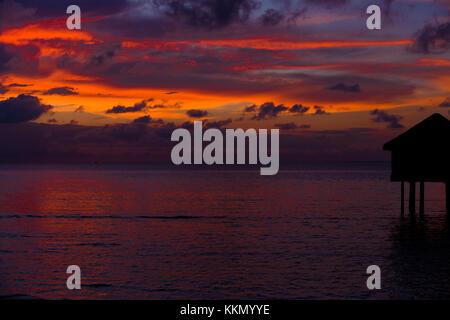 Silhouette di un bungalow sul mare di fronte al tramonto alle Maldive. Il bungalow è situato sul lato destro del Foto Stock