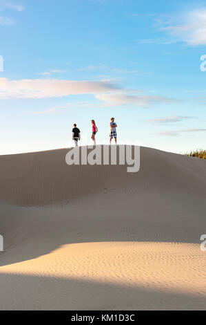Tre adolescenti camminando sul bordo di dune di sabbia in Oceano Dunes State Vehicular Recreation Area, Oceano dune Foto Stock