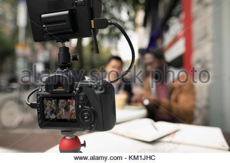 Gli uomini vlogging con videocamera, mangiare a urban cafè sul marciapiede Foto Stock