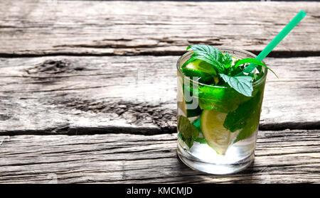 Cocktail mojito . preparata di fresco mojito in vetro con la menta, lime e rum. su di un tavolo di legno. Foto Stock