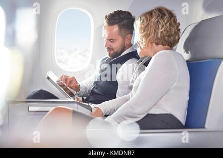 Imprenditore e imprenditrice utilizzando tavoletta digitale su aereo Foto Stock