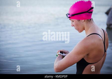 Femmina acqua aperta nuotatore controllo smart guarda al mare Foto Stock