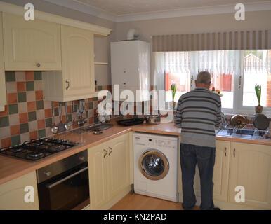 L'uomo lavaggio piatti in cucina Foto Stock