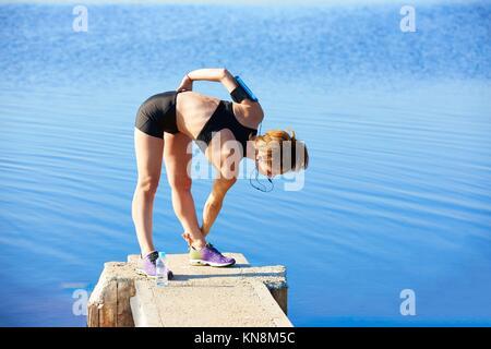 Runner donna stretching in un lago pier all'aperto. Foto Stock