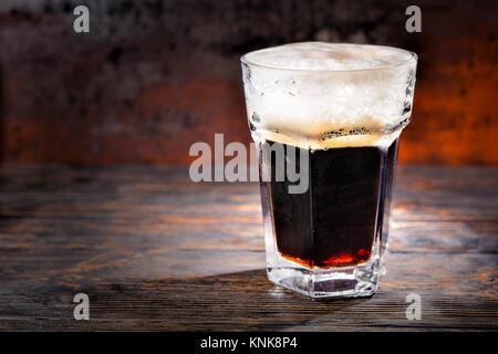 Grande vetro con appena spillata la birra scura e la testa di schiuma sulla scrivania in legno. Cibo e bevande concept Foto Stock