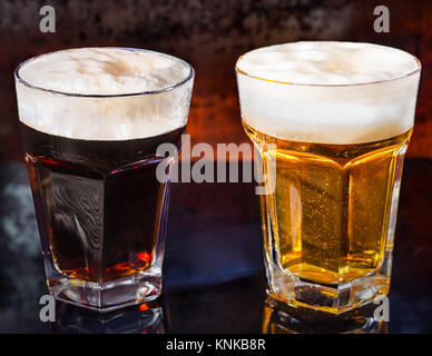 Due bicchieri con spillata di fresco e scuro birra chiara su un nero superficie a specchio. Cibo e bevande concept Foto Stock