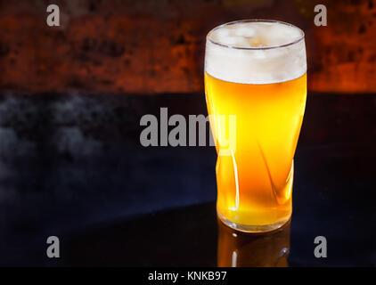Vetro con appena spillata luce non filtrata una birra su di un nero superficie a specchio. Cibo e bevande concept Foto Stock