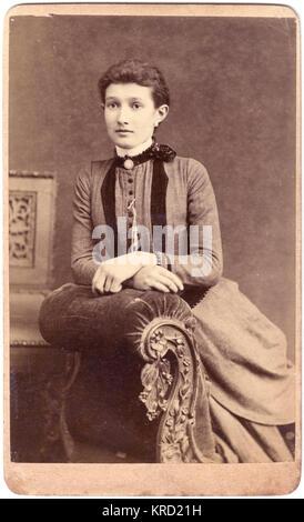 Una giovane donna vittoriana pone per la sua foto in studio, seduto su un ornato chaise longue. Indossa un abito Foto Stock