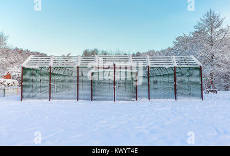 Metallo pallacanestro costruzione coperto di neve pesante Foto Stock