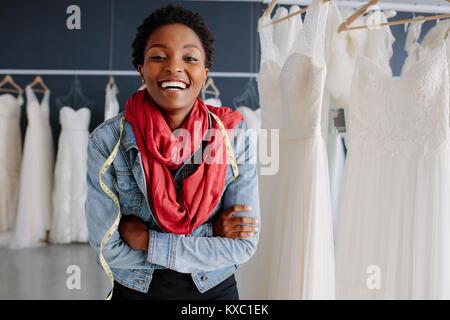 Ritratto di donna africana nuziale con il proprietario del negozio in piedi con le braccia incrociate e sorridente. Foto Stock
