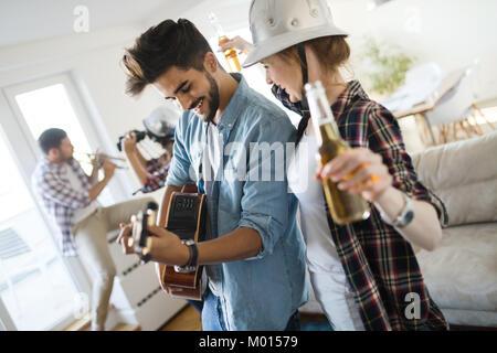 Giovani studenti e amici celebrando ahd divertirsi mentre si beve Foto Stock