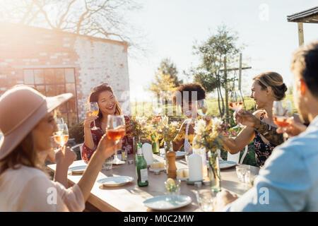Un gruppo di giovani amici appendere fuori con bevande a parte all'aperto. Giovani uomini e donne seduti attorno Foto Stock