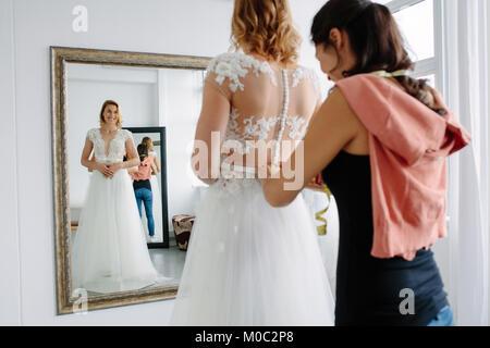 La riflessione a specchio della donna cercando in abito da sposa in un negozio con donne assistant. La donna che Foto Stock