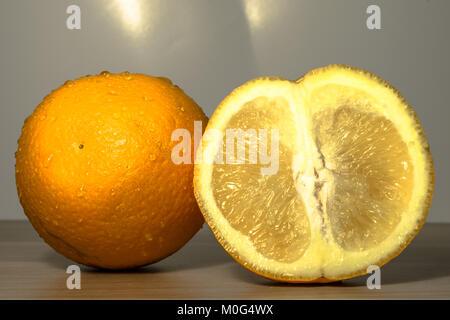 Primo piano di una fetta di un fresco e salutare orange tenuto accanto a un grande tutta arancione mantenuta su Foto Stock