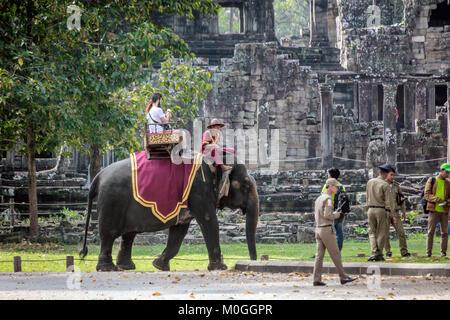I turisti a cavallo di elefante, tempio Bayon, Angkor Thom, Cambogia. Foto Stock