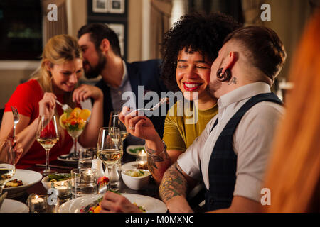 L uomo è baciare il suo partner sulla guancia mentre sono a cena in un ristorante con altri amici. Un altro giovane Foto Stock