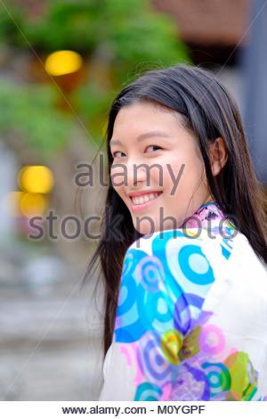 Il vietnamita donna sorridente e indossando un tradizionale Ao Dai vestire Foto Stock