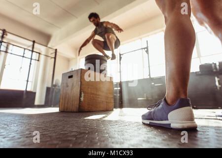Montare il giovane uomo box jumping in corrispondenza di una sezione di formazione palestra di stile. Atleta maschio Foto Stock