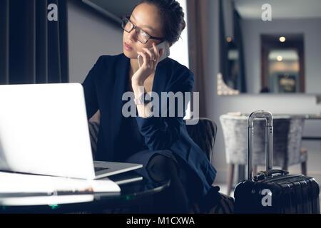 Donna che parla al telefono cellulare durante l'utilizzo di laptop Foto Stock