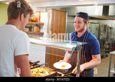Gli studenti adolescenti di essere servito pasto in mensa scolastica Foto Stock