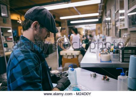Tattoo Artist preparando tatuaggio pistola in tattoo studio Foto Stock