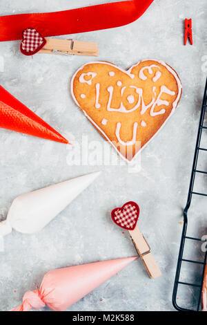 Cottura in forno a forma di cuore i cookie per il giorno di San Valentino, con colorati sacchetto di tubazioni che Foto Stock