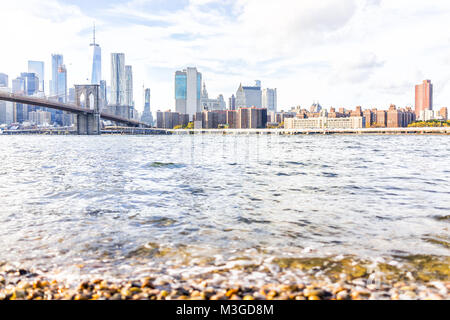 Rocky spiaggia ghiaiosa shore acqua in East River con vista di NYC New York City cityscape skyline e bridge, nessuno Foto Stock