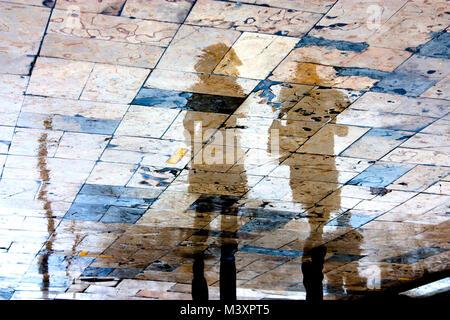Sfocata Rainy day, una persona che cammina sotto ombrellone silhouettes di riflessione sul bagnato city square in Foto Stock