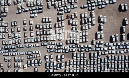 Nuove auto coperto di protezione fogli bianco parcheggiato in una piattaforma di contenimento - riprese aeree Foto Stock