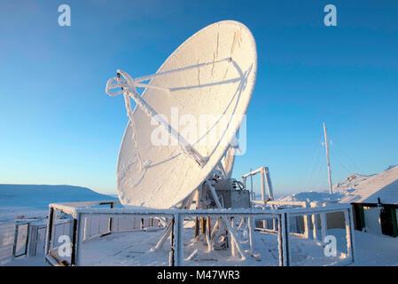Parabola satellitare RICOPERTA DA BRINA contro il cielo blu, Foto Stock