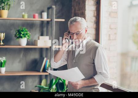 Ritratto di elegante sperimentato vecchio barbuto successo professionale imprenditore qualificato parlando al telefono Foto Stock