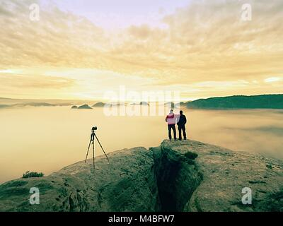 Due calde rivestire i fotografi con treppiede per scattare foto di paesaggio autunnale al di sotto di montagna. Foto Stock